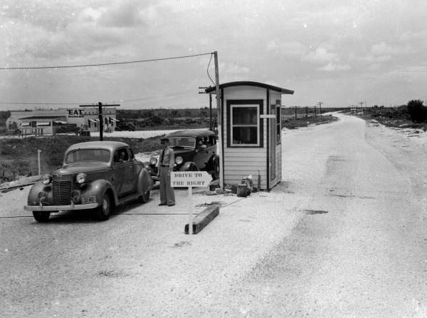 A black and white 1940's photo of a toll booth on Overseas Highway with a car at the toll.