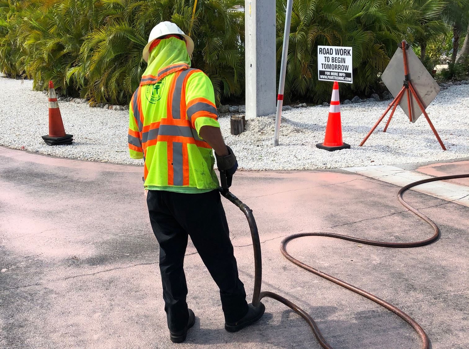 A worker applies pavement preservation liquid on a side road with construction signage behind him.