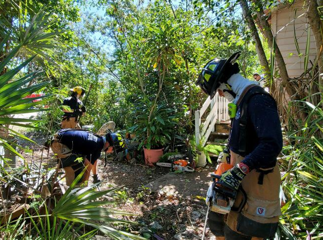 Firefighters seen clearing overgrown landscaping at an elderly person&#39s home